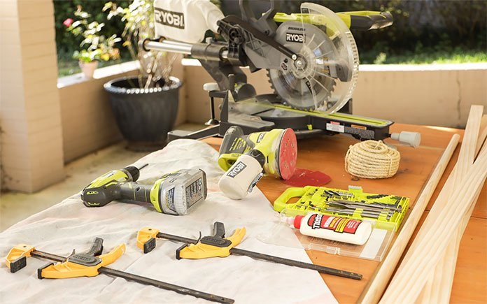 Ryobi and DeWalt power tools laid on an outdoor table