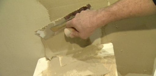 Applying natural clay plaster to wall.