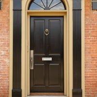 Entry door with door knocker and mail slot.