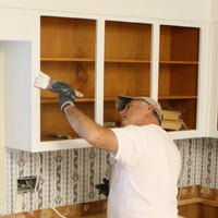 Painter painting kitchen cabinets.