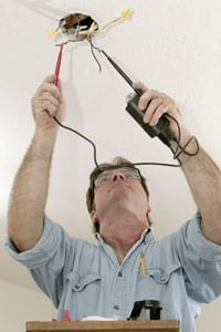 Electrician wiring a ceiling fixture