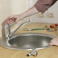 Plumber installing sink faucet
