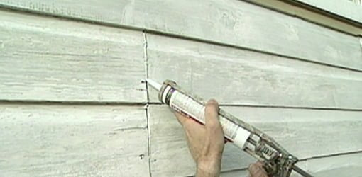 Caulking siding joints.