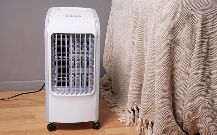 Portable, ventless air conditioner rolled up beside a bed with a spread hanging down and tassels touching the hardwood floor.