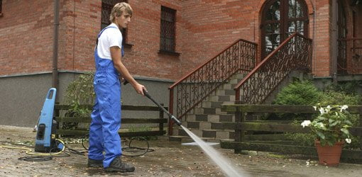 Cleaning a brick patio with pressure washer.