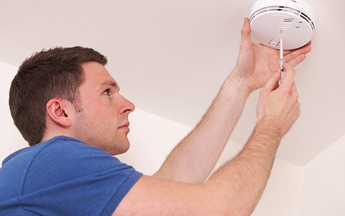 Man in blue shirt installs carbon monoxide detector on ceiling