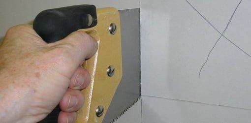 Using a drywall saw to cut through drywall