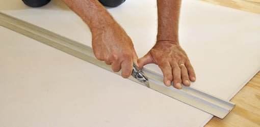 Cutting drywall with straight edge and utility knife.