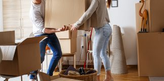 Young man and woman move heavy shipping boxes into their brand new home as a couple