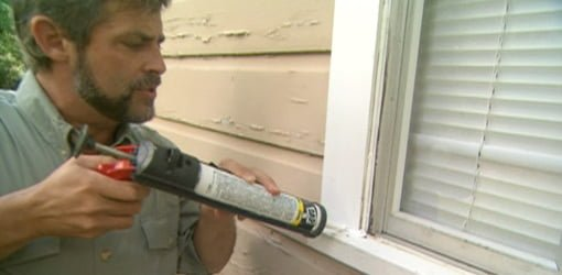 Applying caulking around a windowsill