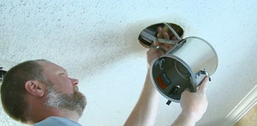 Installing a recessed light fixture in a ceiling.
