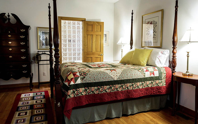Four poster bed with quilt and skirting
