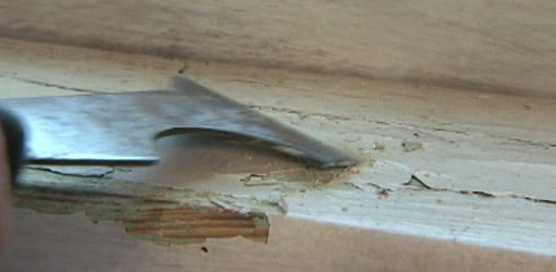 Scraping paint on a windowsill.