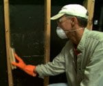 man cleaning mold with brush and mask on