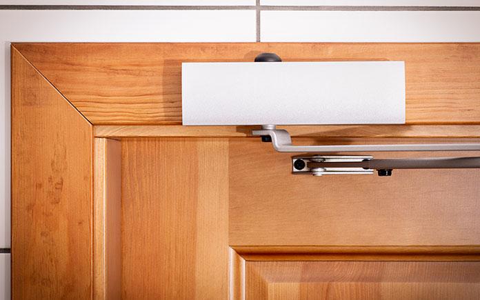 Door closer on a solid wood door, seen close up