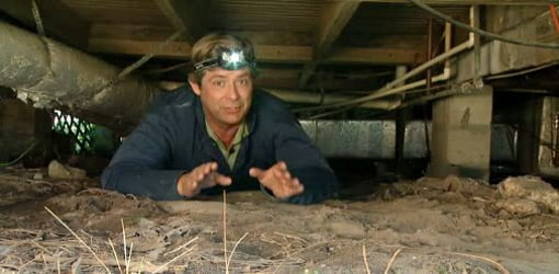 Man with headlamp inspecting crawlspace under house.