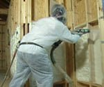 man in protective suit spraying foam insulation