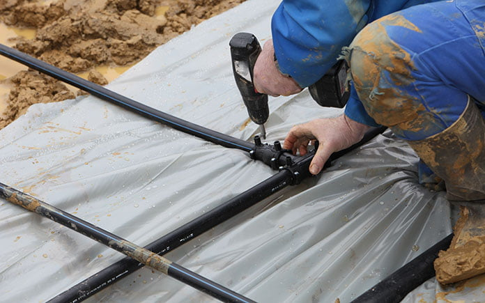 A man installs pipes for a geothermal heat pump