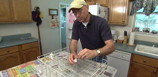 Applying dishwasher rack coating to rusty tines on dishwasher rack.