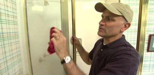 Joe Truini cleaning a glass shower door with vinegar.