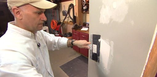 Using drywall knife to apply joint compound to drywall repair