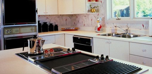 Kitchen with island cooktop and built-in cabinet range.