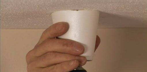 Drilling in ceiling with foam cup to collect dust.