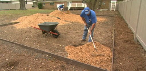 Men with rake adding wood mulch to play area.