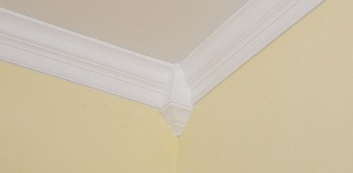 Crown molding with corner block on yellow wall.