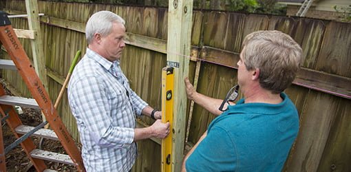 Danny Lipford and Allen Lyle ensure the new fence post is level.