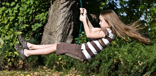 Child swinging on a tree swing.