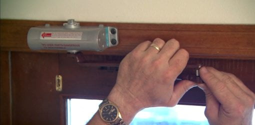 Installing a pneumatic door closer.