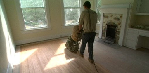 Using a drum sander to sand a wood floor.