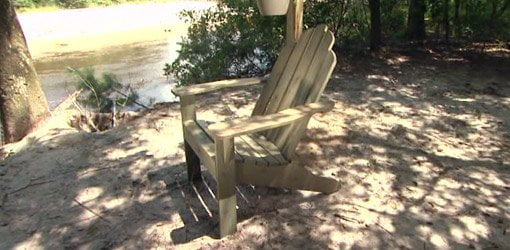 Adirondack chair on sandy beach next to a river