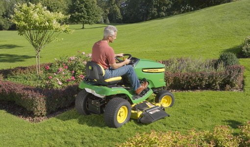 Mowing a lawn with a John Deere riding mower.