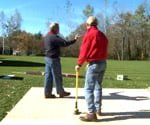two men in a yard planning a shed
