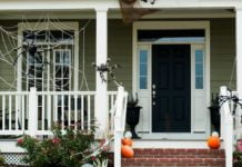 Home's entry decorated for Halloween with fake spiders and jack-o-lanterns