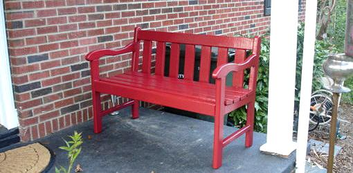Refinished red painted bench on porch