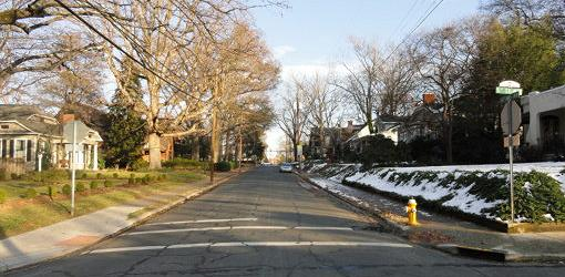 Street with clear yards on left and snow in yards on right