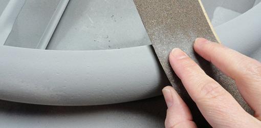 Sanding metal between coats of paint.