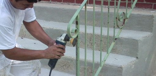 Using a rotary wire bursh attachment to remove rust on porch railings.