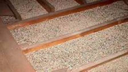 Vermiculite insulation between floor joists in attic.