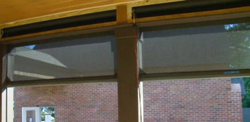 Retractable screens being lowered on a porch