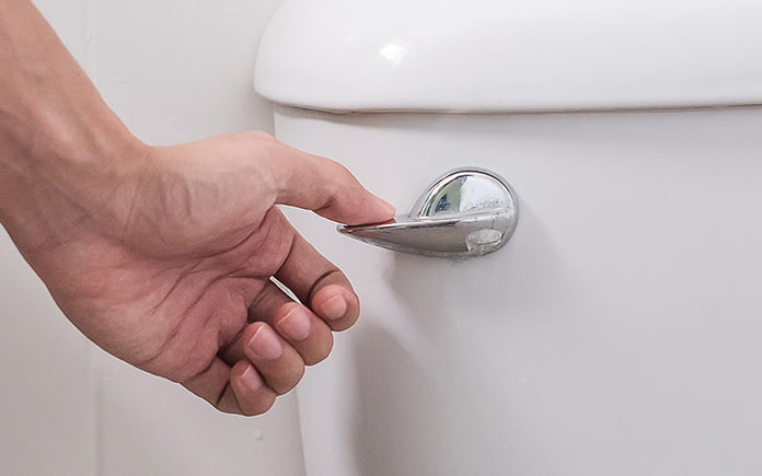 Woman's hand flushes toilet that has a stuck handle