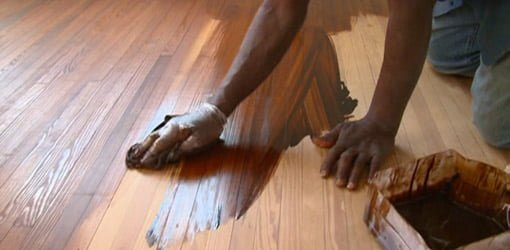 Staining heart pine floors by hand with a rag