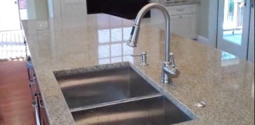 Kitchen sink and faucet installed in granite countertop