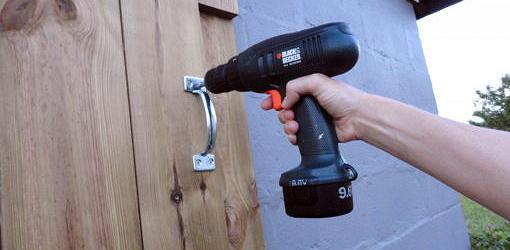 Cordless drill screwing in screw on door