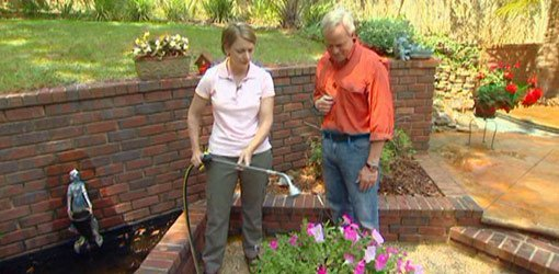 Julie Day and Danny Lipford watering plants