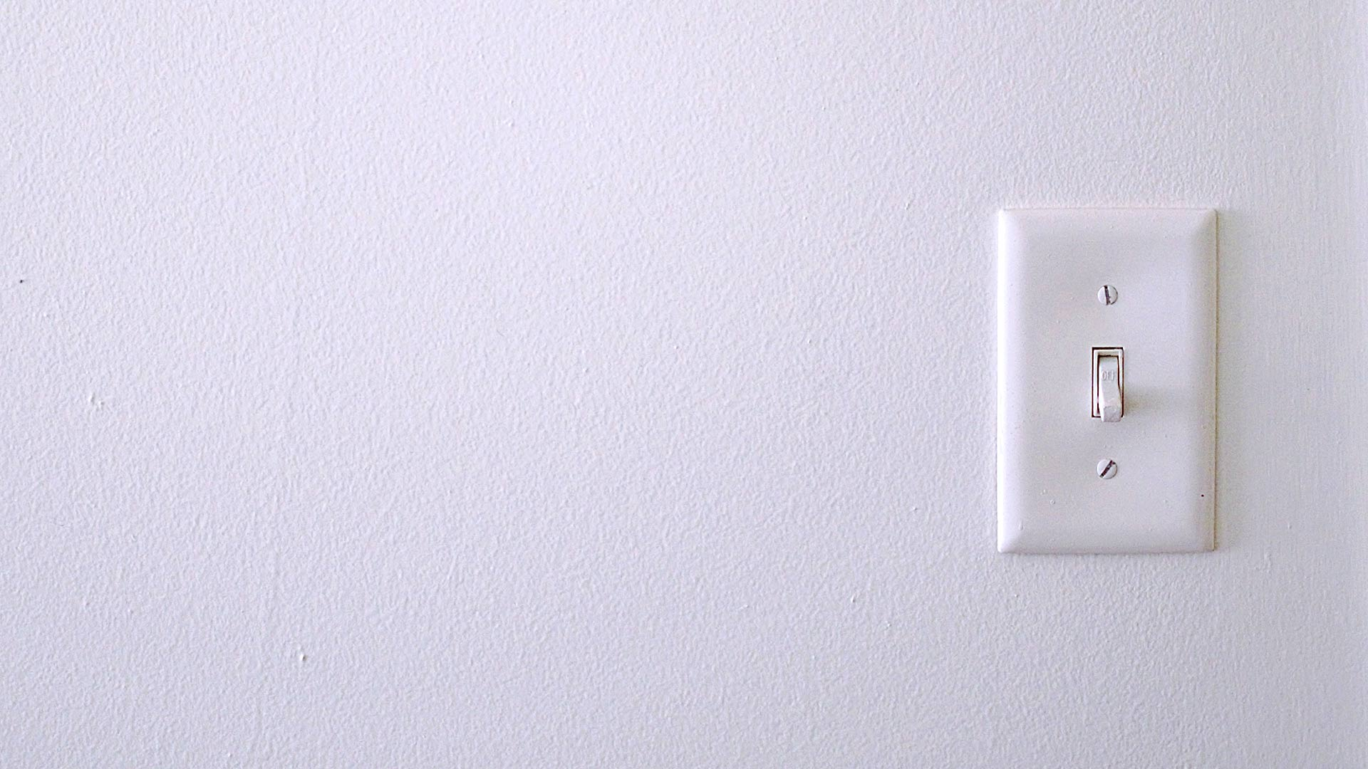Single-pole light switch on a white wall