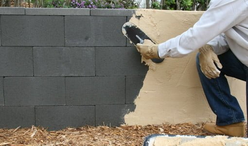 Applying surface-bonding cement to a dry-stacked, concrete block wall